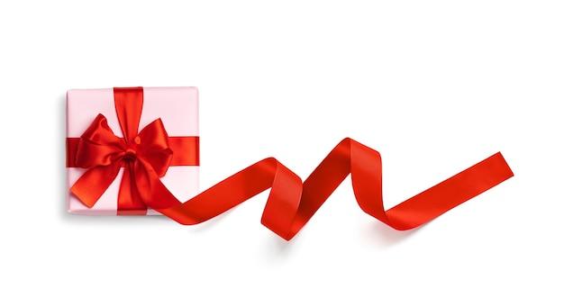 Różowe pudełko z czerwoną wstążką na białym tle. widok z góry. leżał płasko.