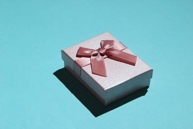 Różowe pudełko z kokardą na niebieskim tle pastelowych z bliska. koncepcja wakacje, urodziny