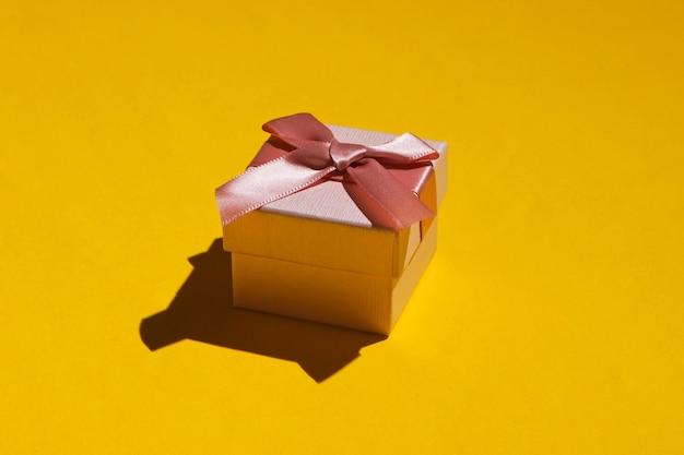 Różowe pudełko z kokardą na żółtym tle z bliska. koncepcja wakacje, urodziny