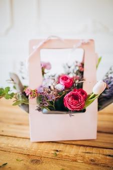 Różowe pudełko z kwiatami. pudełko z różami piwonii i białymi tulipanami. kwiaty ogrodowe w doniczkach. kwiaty.
