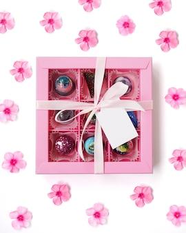 Różowe pudełko z ręcznie robionymi czekoladkami na białym z różowymi kwiatami