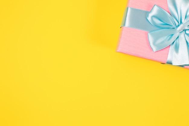 Różowe pudełko związane z niebieską wstążką z kokardą na górze na żółtym tle. skopiuj miejsce na tekst. minimalne płaskie ułożenie.