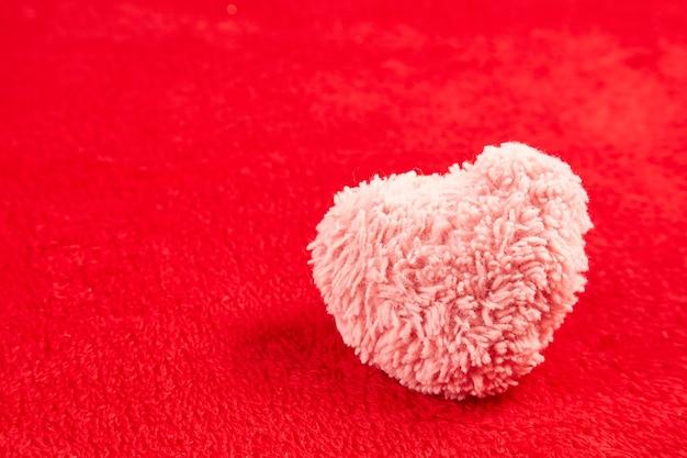 Różowe puszyste serce na tle czerwonego futra