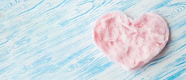 Różowe pyszne serduszko wykonane ze słodkiej waty cukrowej na niebieskim tle. modny minimalistyczny styl graficzny, baner