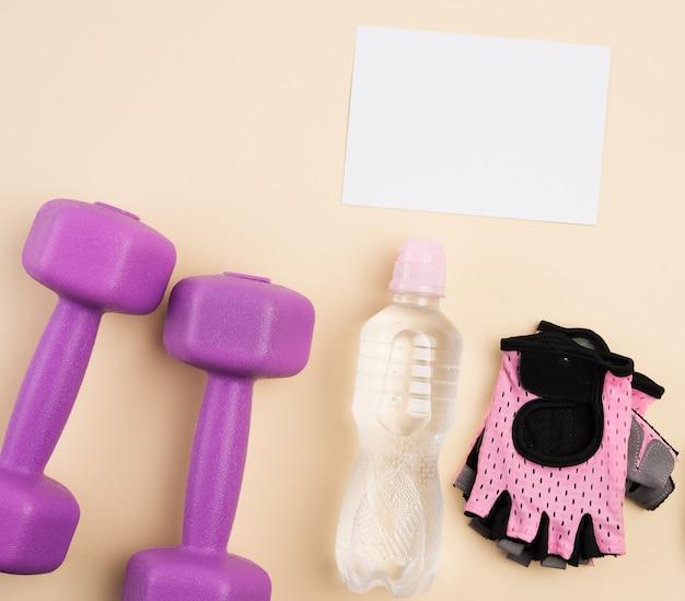 Różowe rękawiczki sportowe, para fioletowych hantli i butelka wody na beżowym tle, widok z góry, zdrowy styl życia