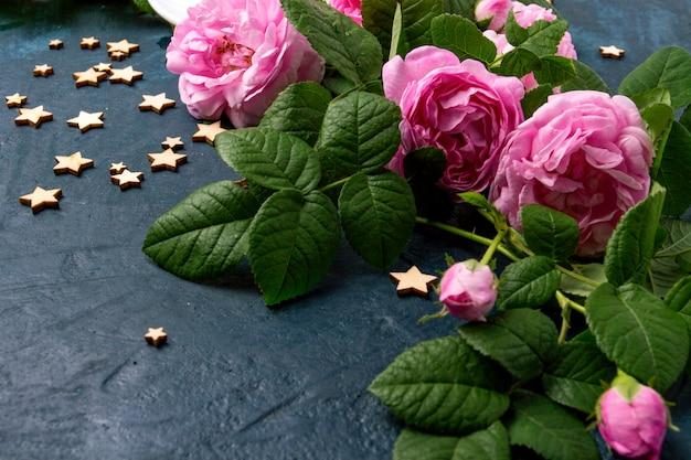 Różowe róże i gwiazdy na ciemnoniebieskiej powierzchni. pojęcie kawy