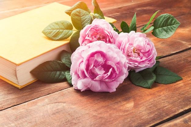Różowe róże i książka z żółtą okładką na drewnianej powierzchni