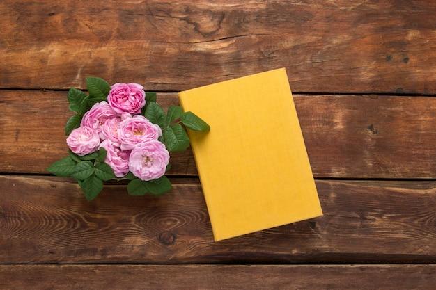 Różowe róże i książka z żółtą pokrywą na drewnianym tle. pojęcie romantycznych opowieści i powieści. leżał płasko, widok z góry