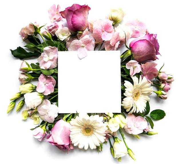 Różowe róże i kwiaty w ramce z białym kwadratem dla tekstu na białym tle