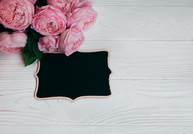 Różowe róże i ramka na zdjęcia na białym stole