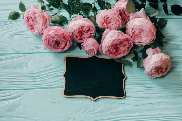 Różowe róże i ramka na zdjęcia na niebieskim stole