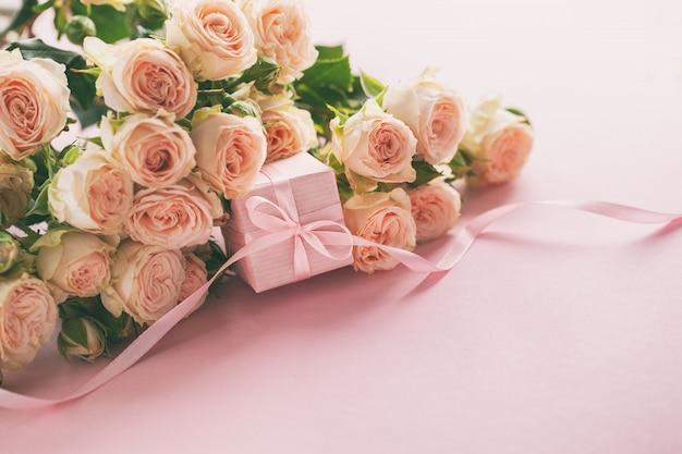 Różowe róże kwitną i prezent lub teraźniejszości pudełka różowy tło.