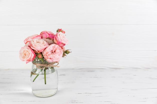 Różowe róże kwitną w szklanym słoju na białym drewnianym textured tle