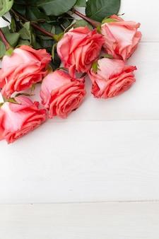 Różowe róże na białym drewnianym tle