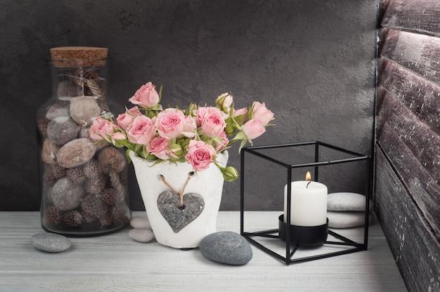 Różowe róże w betonowym garnku ze świecą