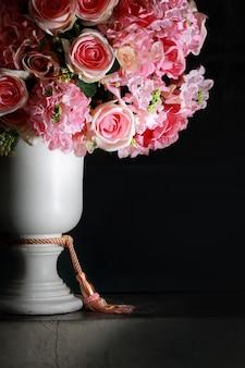 Różowe róże w białej rzymskiej wazonie