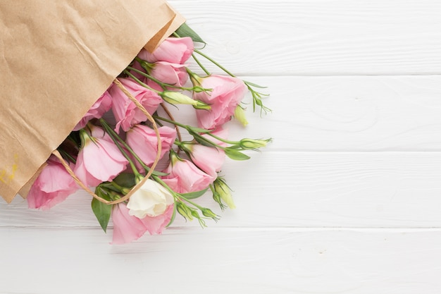 Różowe róże w papierowej torbie z kopii przestrzenią