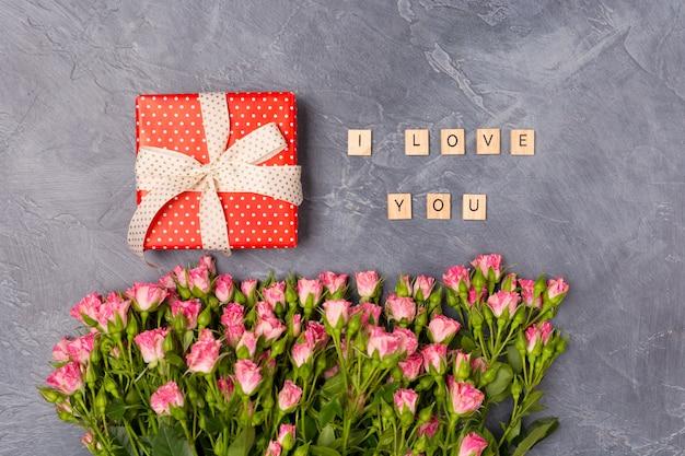Różowe róże w sprayu, czerwone pudełko i kocham cię tekst na szarym tle. dzień matki koncepcja walentynki świętego walentego