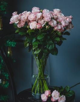 Różowe róże w szklanym wazonie z wodą