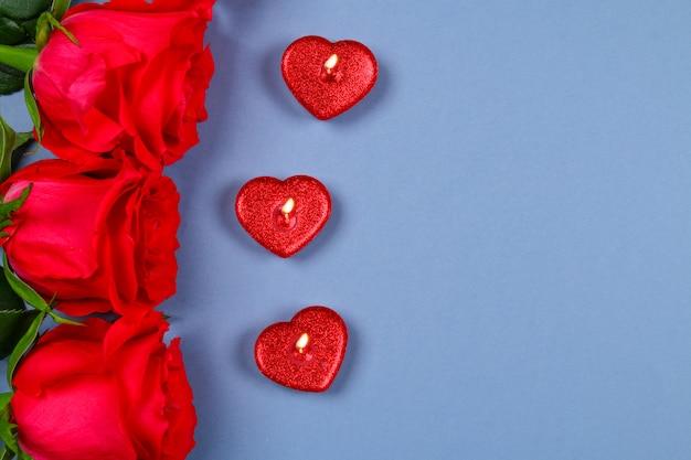 Różowe róże z czerwonymi świeczkami w kształcie serca. 8 marca, dzień matki, walentynki.
