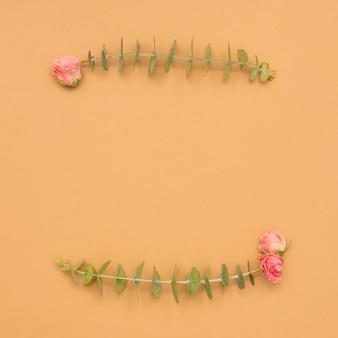 Różowe róże z liśćmi eukaliptusa gałązką nad brązową powierzchnią