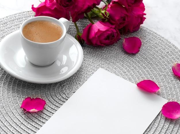 Różowe róże z pustą kartkę z życzeniami i filiżankę kawy na różowym marmurze
