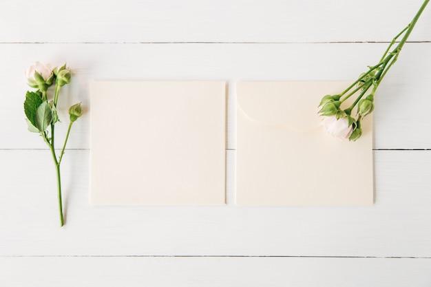 Różowe róże z pustymi kopertami minimalistyczne płaskie laywhite drewniane tło
