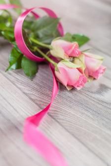 Różowe róże ze wstążką na drewnie