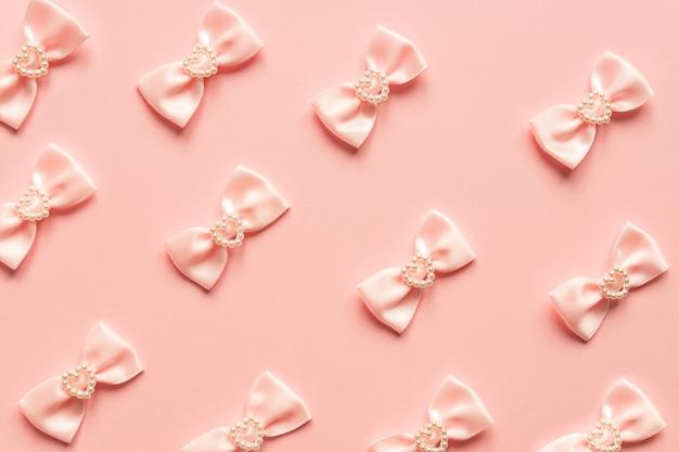 Różowe satynowe kokardki w perłowe serduszka na różowym tle. świąteczna koncepcja na walentynki.
