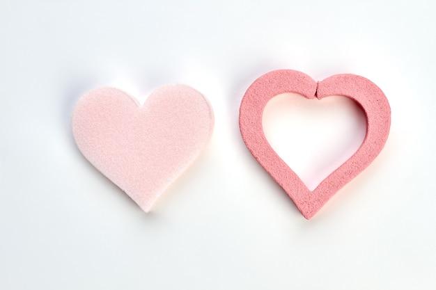 Różowe serca na białym tle. gąbka w kształcie serca na białym tle. pielęgnacja ciała i skóry.