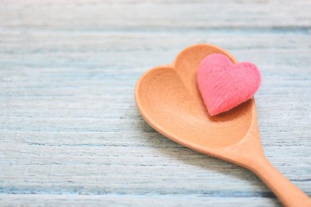 Różowe serce na drewnianej łyżce i na drewnianej ścianie stołu, widok z góry / kształt serca łyżka do kawy, uwielbiam zdrowie lub uwielbiam gotować