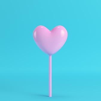 Różowe serce na patyku na jasnym niebieskim tle