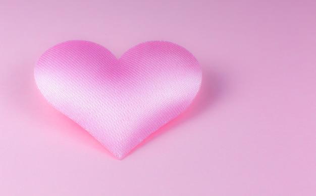 Różowe serce na różowym tle. koncepcja dzień świętego walentego. miłość i romantyczne zdjęcie. pocztówka na wakacje. piękna ciepła tapeta z miłością. nieostrość. skopiuj miejsce.