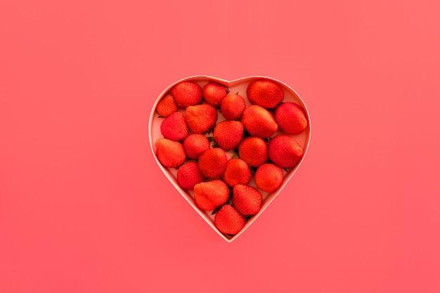 Różowe serce pudełko na walentynki na różowym tle z truskawkami.