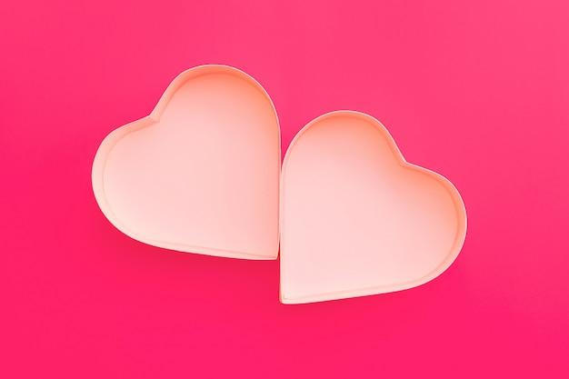 Różowe serce pudełko na walentynki na różowym tle.