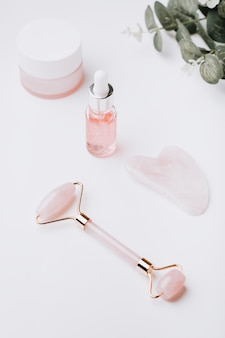 Różowe serum kwasu hialuronowego, wałek z różowego kwarcu, gua sha i nawilżający krem do twarzy na białym blacie. kosmetyki i narzędzia przeciwstarzeniowe na białym, kopiuj przestrzeń, widok z góry, baner internetowy