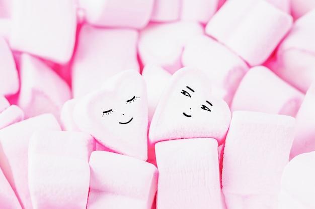 Różowe słodkie ptasie mleczko z śmieszną uśmiechniętą twarzą
