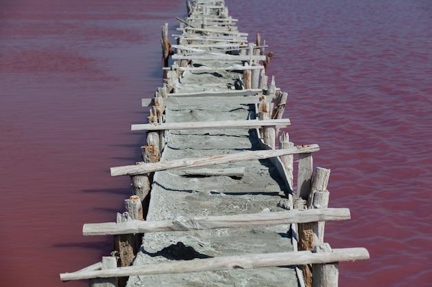 Różowe słone jezioro z leczniczym błotem, unikalnymi algami i mikroorganizmami. most lub prowizoryczna tama.