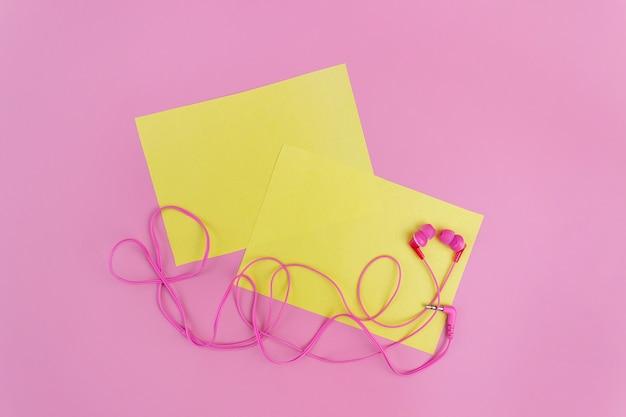 Różowe słuchawki do projektowania koncepcyjnego. makieta pustego żółtego arkusza na różowym tle. mieszkanie świeckich, kopia przestrzeń. nowoczesny styl