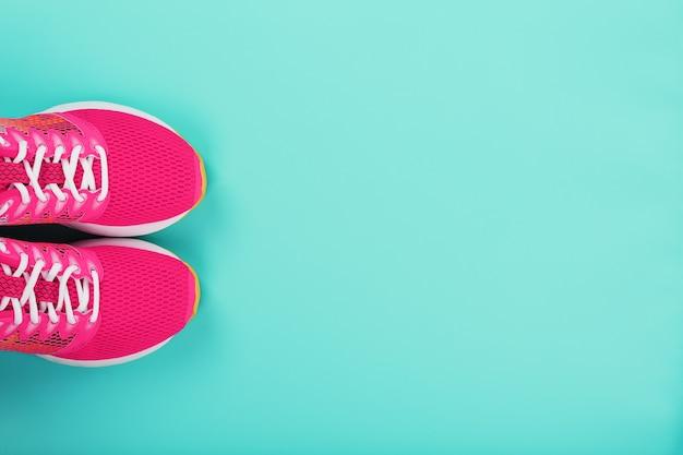 Różowe sportowe trampki do biegania na niebieskim tle z wolną przestrzenią. widok z góry, minimalistyczna koncepcja