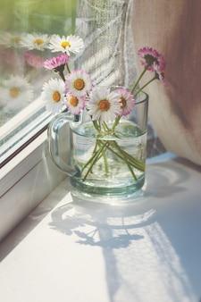 Różowe stokrotki na parapecie, bukiet polnych kwiatów w szklanym kubku przy oknie