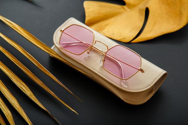 Różowe stylowe okulary przeciwsłoneczne na ciemnym czarnym tle ze złotymi liśćmi palmowymi. modna, modna optyka w złotej obudowie.