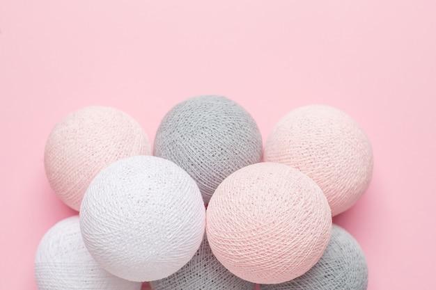 Różowe, szare i białe kulki na pastelu