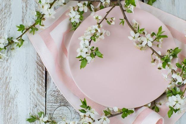Różowe talerze, serwetki i gałęzie kwiatów wiśni