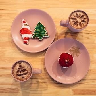 Różowe talerze z cukierkami świątecznymi stoją między kubkami z kawą na drewnianym stole