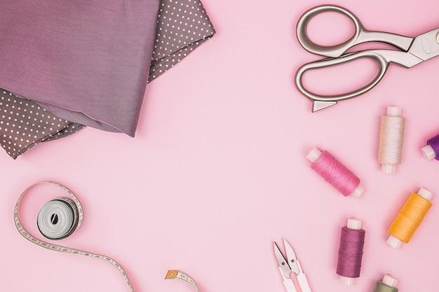Różowe tło z akcesoriami do szycia i tkaniną. nici szwalnicze, igły, tkanina, centymetr krawiecki lub taśma miernicza. widok z góry, kopia przestrzeń. materiały krawieckie.