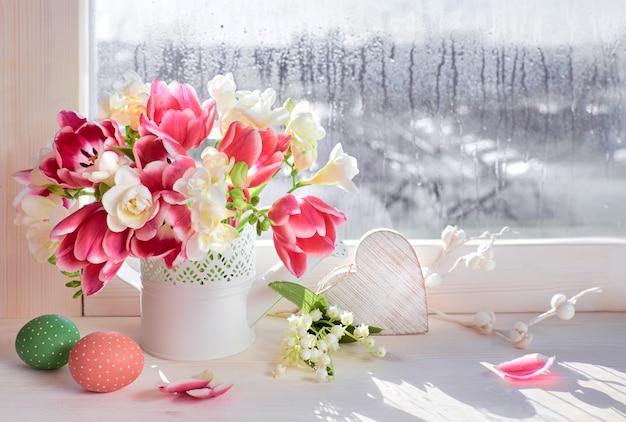 Różowe tulipany i białe kwiaty frezji z dekoracjami wielkanocnymi na desce okna