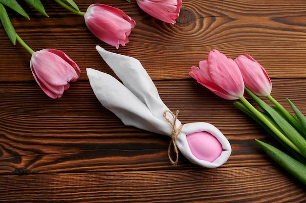 Różowe tulipany i pisanka na drewnianym stole. wiosenne kwiaty kwitnące i paschalne jedzenie, świeża dekoracja kwiatowa na święta