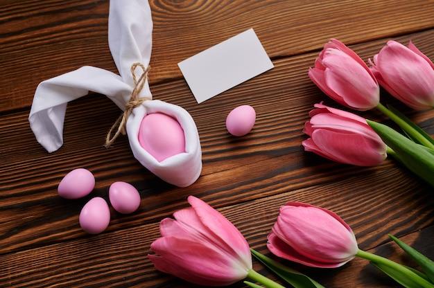 Różowe tulipany i pisanka na drewnianym tle