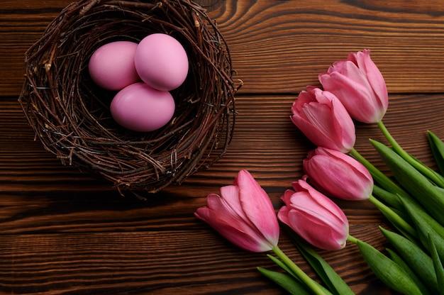 Różowe tulipany i pisanki w ozdobne gniazdo na drewnianym stole. wiosenne kwiaty kwitnące i paschalne jedzenie, świeża dekoracja kwiatowa, symbol święta